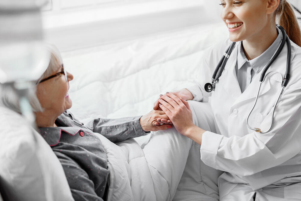 Female physician holding hands with elderly patient.